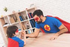 Père et fils dans les costumes des super héros Ils concurrencent dans le bras de fer Ils sont mesure leur force Photos stock