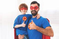 Père et fils dans les costumes rouges et bleus des super héros Sur leurs visages sont les masques et ils sont dans des imperméabl Photo stock