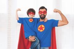 Père et fils dans les costumes rouges et bleus des super héros Sur leurs visages sont les masques et ils sont dans des imperméabl Photos stock