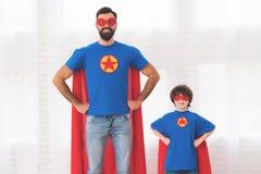 Père et fils dans les costumes rouges et bleus des super héros Sur leurs visages sont les masques et ils sont dans des imperméabl Photographie stock