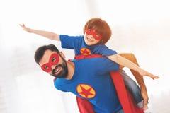 Père et fils dans les costumes rouges et bleus des super héros Sur leurs visages sont les masques et ils sont dans des imperméabl Image stock