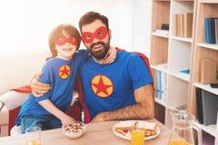Père et fils dans les costumes rouges et bleus des super héros Sur leurs visages sont les masques et ils sont dans des imperméabl Photos libres de droits