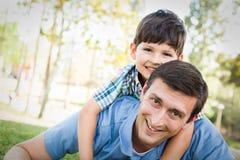 Père et fils de métis jouant ensemble en parc Photos libres de droits