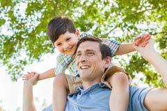 Père et fils de métis jouant sur le dos ensemble en parc Image stock