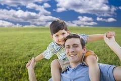 Père et fils de métis jouant sur le dos sur le champ d'herbe Photos libres de droits