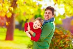 Père et fils de sourire ayant l'amusement dans le parc d'automne Images libres de droits