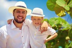 Père et fils de sourire des vacances d'été près du bord de la mer tropical Images stock