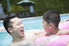 Père et fils de sourire jouant dans la piscine Image stock