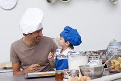 Père et fils de sourire mangeant les biscuits faits maison images libres de droits