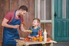 Père et fils de sourire préparant le hot-dog ensemble dans l'arrière-cour image stock