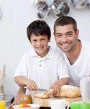 Père et fils de sourire préparant un pain grillé Images libres de droits