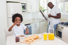 Père et fils de sourire prenant un petit déjeuner Photographie stock libre de droits