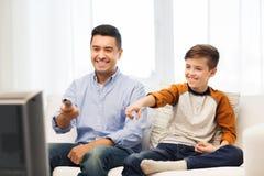 Père et fils de sourire regardant la TV à la maison Image libre de droits