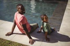 Père et fils de sourire s'asseyant sur le bord de la piscine Image libre de droits