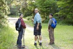 Père et fils de vue arrière trimardant en bois sur le journal Photo stock
