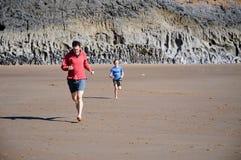 Père et fils emballant sur la plage Image libre de droits