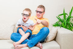 Père et fils en verres 3D regardant la TV Photo stock