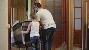 Père et fils entrant un berceau dans une salle banque de vidéos