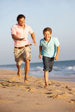 Père et fils exécutant le long de la plage d'été photo libre de droits