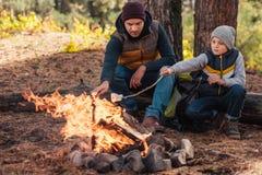 père et fils faisant cuire des guimauves au feu de camp photo libre de droits