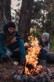 père et fils faisant cuire des guimauves au feu de camp photo stock