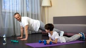 Père et fils faisant la séance d'entraînement à la maison, garçon encourageant de papa pour s'exercer, motivation photo libre de droits
