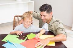 Père et fils faisant les formes de papier ensemble à la table Image libre de droits
