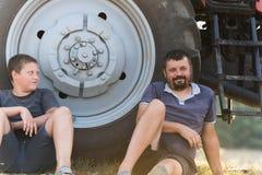 Père et fils faisant une pause après dur labeur au champ photo libre de droits
