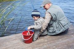 Père et fils fihsing à un lac Photographie stock libre de droits