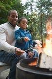Père et fils grillant des guimauves images stock