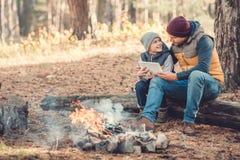 père et fils heureux à l'aide du comprimé numérique tout en se reposant sur le rondin photos libres de droits