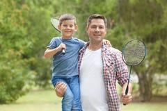 Père et fils heureux avec des raquettes de tennis Photo stock