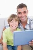 Père et fils heureux avec le comprimé numérique photographie stock