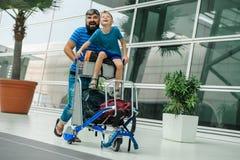 Père et fils heureux et excités ensemble pour le voyage, garçon s'asseyant et encourageant sur le chariot à bagages Vacances ab d Image libre de droits