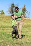 Père et fils jouant à l'extérieur Images stock