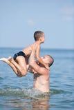 Père et fils jouant à la mer photographie stock
