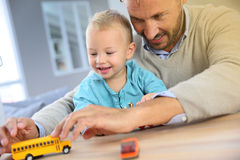 Père et fils jouant avec des jouets à la maison ayant l'amusement Images libres de droits
