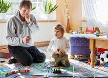 Père et fils jouant avec des voitures de course sur le champ de courses, à l'intérieur, t Images stock