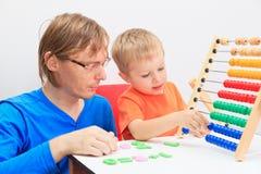 Père et fils jouant avec l'abaque Images libres de droits