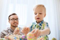 Père et fils jouant avec l'argile de figuline à la maison Image libre de droits