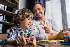 Père et fils jouant avec le modèle d'atomes Image libre de droits