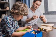 Père et fils jouant avec le modèle d'atomes Images libres de droits