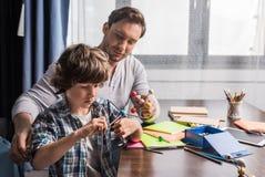 Père et fils jouant avec le modèle d'atomes Image stock