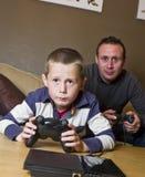 Père et fils jouant des jeux vidéo Photo stock