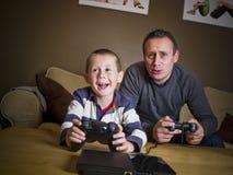 Père et fils jouant des jeux vidéo Image stock