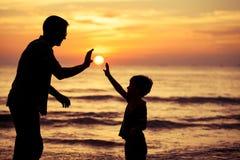 Père et fils jouant en parc au temps de coucher du soleil Photographie stock