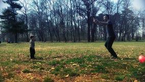 Père et fils jouant le football en parc banque de vidéos