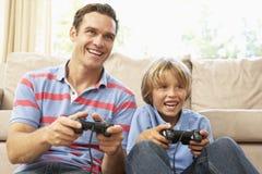 Père et fils jouant le jeu d'ordinateur Photos stock