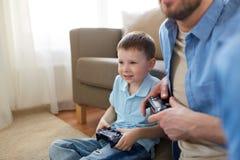 Père et fils jouant le jeu vidéo à la maison Image stock