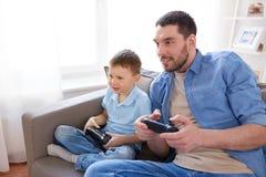 Père et fils jouant le jeu vidéo à la maison Images libres de droits